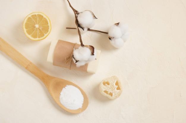 Bicarbonate de soude dans une cuillère en bois, savon, luffa, citron et fleur de coton sur fond beoge vue de dessus de l'espace de copie