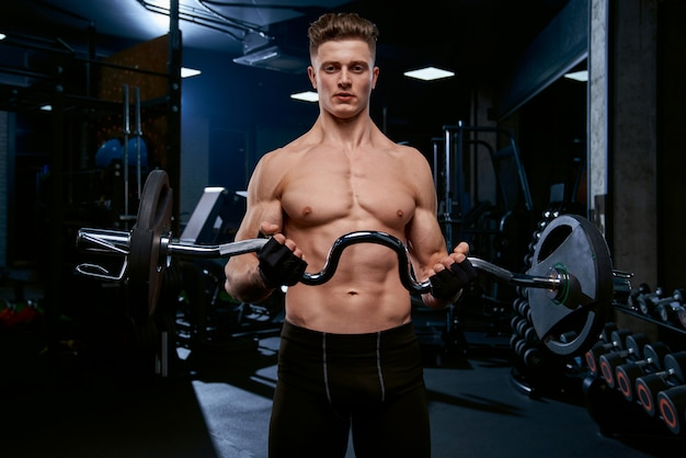Biceps d'entraînement sportif torse nu avec haltères.