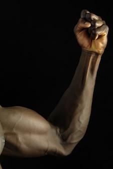 Biceps d'un garçon africain avec un fond noir