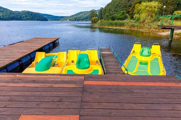 Bicyclettes d'eau jaune verrouillé au quai du lac marina aux beaux jours d'été
