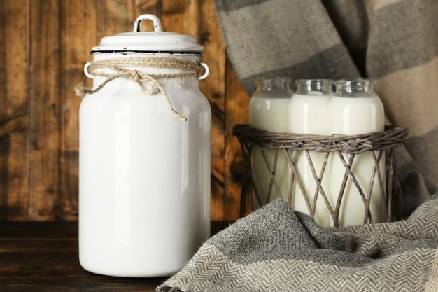 Bidon de lait et bouteilles en verre sur bois rustique