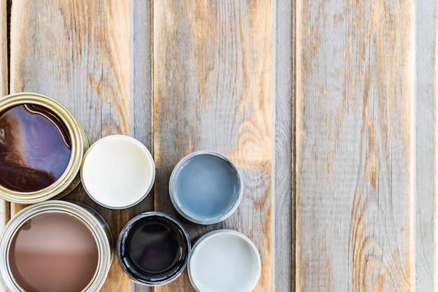 Bidons ouverts de différentes peintures, vernis et teintures