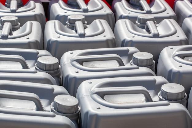 Bidons en plastique de couleur grise dans l'entrepôt, la production, l'usine. surface des bidons en plastique