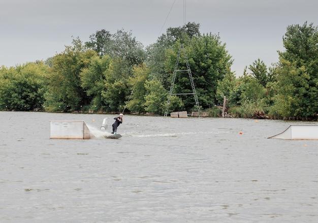Bielawa, pologne. 03/06/2020 wawa wake. une jeune athlète féminine glisse sur des skis nautiques sur les vagues du lac. fille à cheval sur le wakeboard