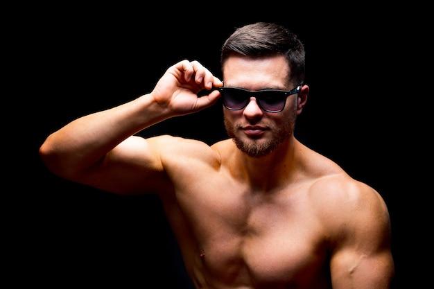 Bien construire un bel homme sans chemise qui pose en studio. corps fort et visage frais. homme portant des lunettes. portrait. mise au point sélective. fermer.