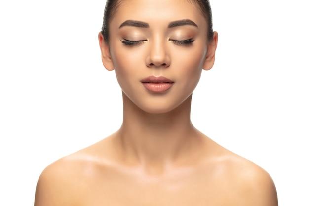 Bien entretenu. portrait de la belle jeune femme sur fond de studio blanc. concept de cosmétiques, maquillage, traitement naturel et écologique, soins de la peau. look brillant et sain, mode, soins de santé. copyspace.