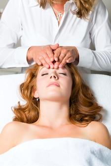 Bien-être, femme se faisant masser la tête à spa