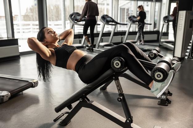 Le bien-être. jeune femme caucasienne musclée pratiquant dans une salle de sport avec équipement. modèle féminin athlétique faisant des exercices abs, entraînant le haut du corps, le ventre. bien-être, mode de vie sain, musculation.