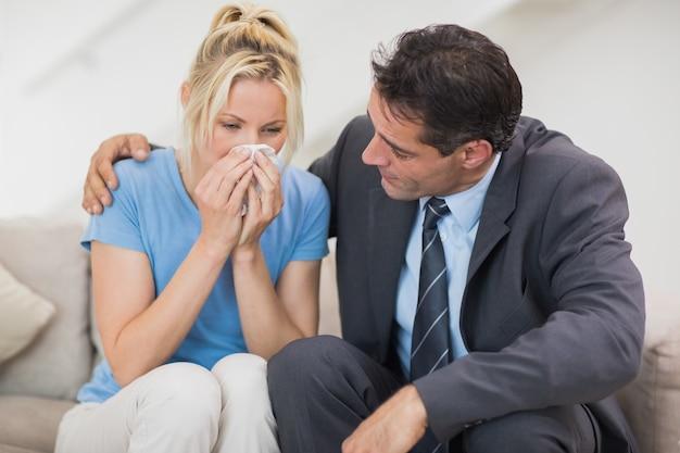 Bien habille l'homme consolant une femme dans le salon
