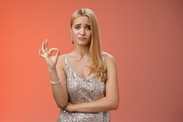 Et bien pas mal. hésitant incertain mignonne élégante copine blonde riche en robe argentée fronçant les sourcils grincant des sourcils spectacle douteux ok geste normal pas très impressionné choix d'un ami incertain, fond rouge.
