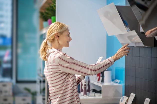 Biens de consommation. cliente blonde choisissant des produits dans une salle d'exposition et à la recherche de participation