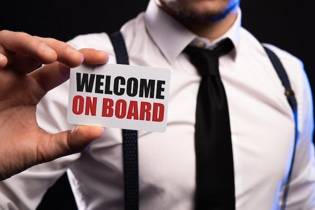 Bienvenue à bord homme d'affaires tenant une pancarte blanche avec texte au bureau