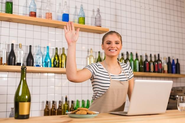 Bienvenue chez nous. amical ravi femme positive debout au comptoir et agitant sa main tout en vous saluant