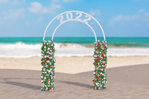 Bienvenue dans le concept du nouvel an 2022. beau décor arc, porte ou portail avec des fleurs et signe 2022 sur un gros plan extrême de la côte déserte de l'océan. rendu 3d