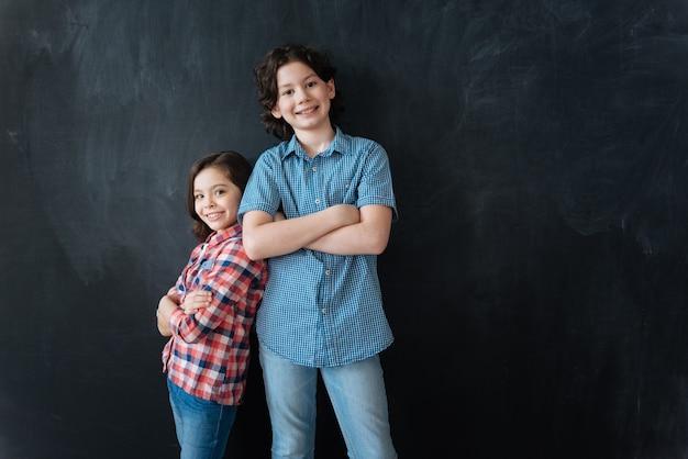 Bienvenue dans notre équipe. des enfants décisifs charmants et sympathiques debout dans un tableau noir et appréciant le dessin imaginaire tout en se tenant dos à dos