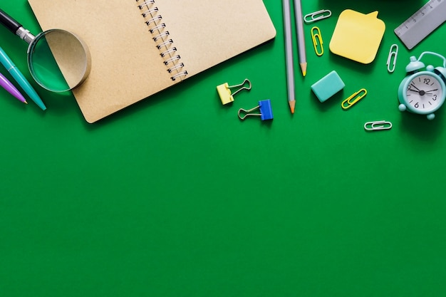 Bienvenue à l'école. fournitures de bureau sur une commission scolaire verte. diverses fournitures scolaires sur un fond vert minable. concept de vente d'école
