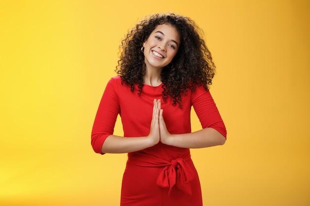 Bienvenue à l'intérieur. portrait d'une hôte féminine sympathique et polie en robe rouge avec des cheveux bouclés tenant la main dans un geste de namaste inclinant la tête et souriant en invitant des invités dans un style asiatique.