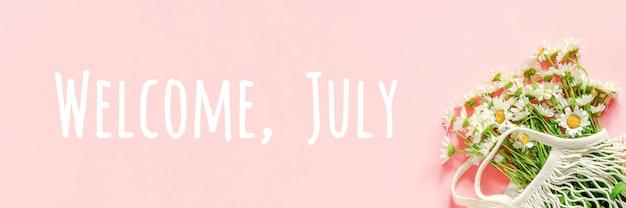 Bienvenue, texte de juillet. bouquet de camomille blanche dans un sac en filet écologique réutilisable sur rose