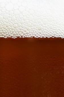 Bière. beau détail de verre battu de bière avec de la mousse. abstrait arrière-plan coloré.