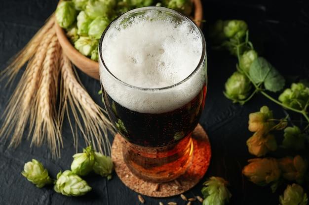 Bière, blé et hop sur table noire