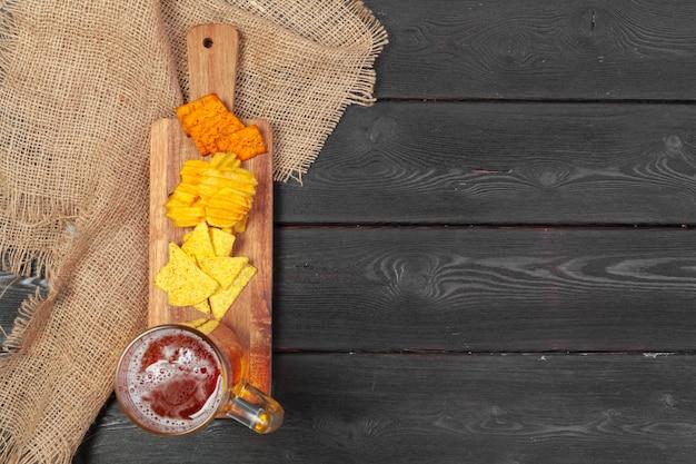 Bière blonde et des collations sur fond de table en bois.