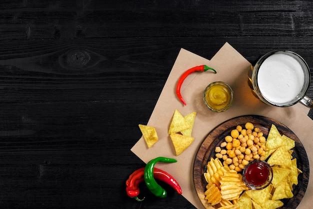 Bière blonde et collations sur table en bois noir chips de noix vue de dessus avec fond