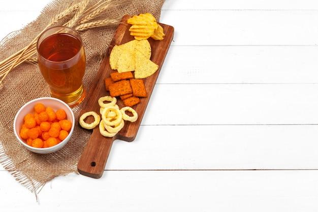 Bière blonde et collations sur table en bois.
