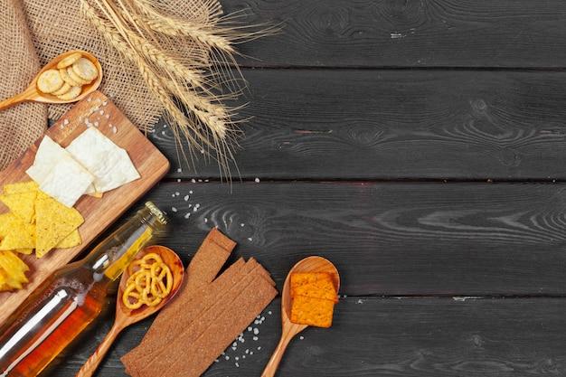 Bière blonde et des collations sur une table en bois.