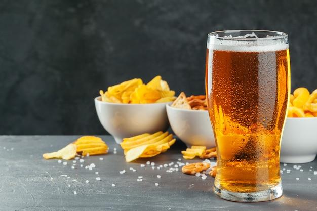 Bière blonde et des collations sur la table en pierre. cracker, chips vue de côté