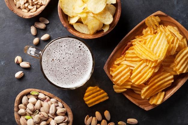 Bière blonde et des collations sur la table en pierre