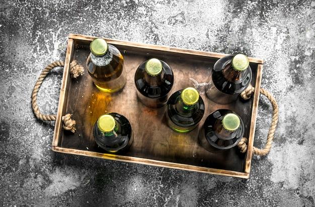Bière en bouteilles sur un plateau en bois. sur un fond rustique.