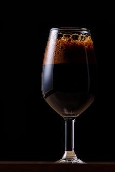 Bière brune dans un verre sur un mur sombre.