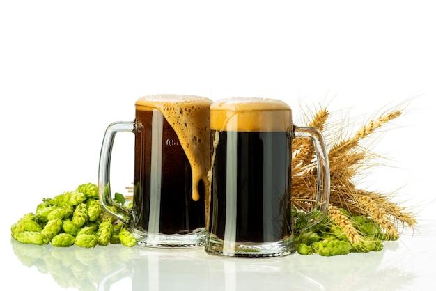Bière brune avec de la mousse dans des verres et du houblon et du blé sur fond blanc