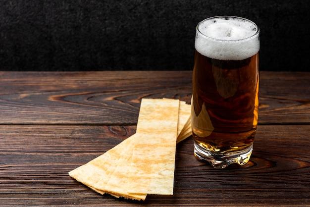 Bière et chips sur fond en bois foncé.