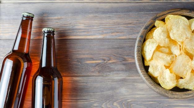 Bière et chips de pommes de terre salées sur une assiette sur un bois brun