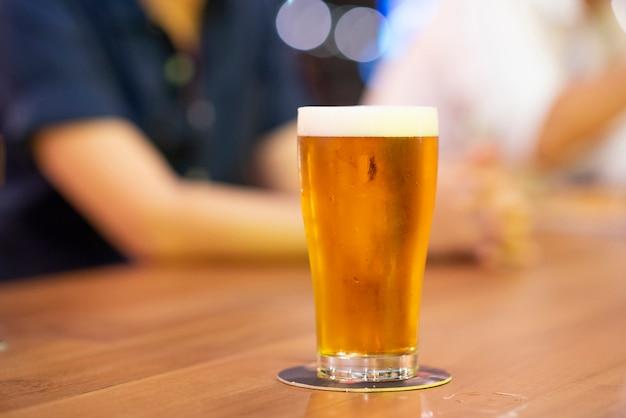 Bière dans le long verre sur la table dans le bar de nuit.