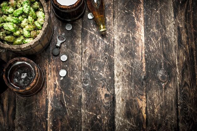 Bière dans une tasse en bois avec du houblon vert sur une table en bois.
