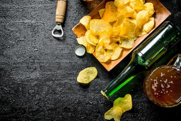 Bière dans des tasses et une bouteille de chips sur une assiette. sur fond rustique noir