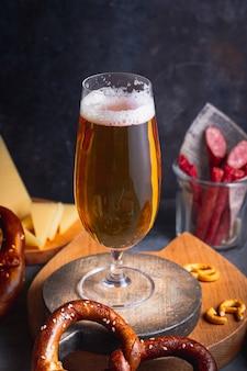 Bière dans le verre avec assortiment de snacks à la bière brezel cheese chips saucisses