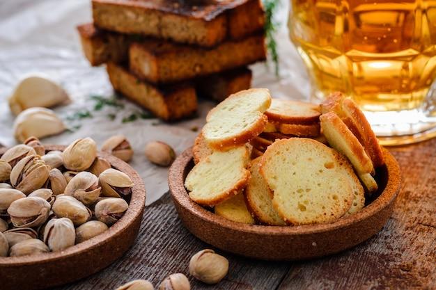 Bière dans un verre, pistaches, croûtons de seigle et craquelins sur une table en bois