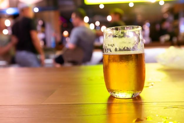 Bière dans le verre sur la table du bar de nuit.