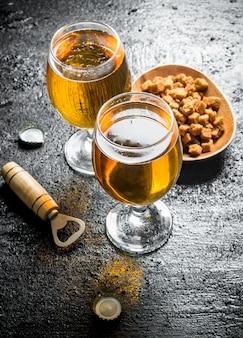 Bière dans des verres et miettes sur une assiette. sur fond rustique noir