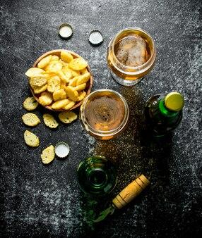 Bière dans des verres et miettes dans un bol. sur table rustique