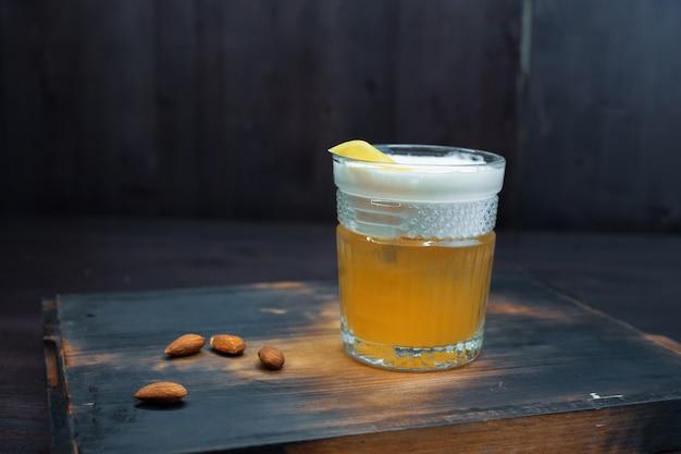 Bière dorée avec de la mousse blanche dans un verre à bière se tient sur une table en bois noire dans le bar. la boisson est décorée d'arachides. servi frais. profiter du week-end