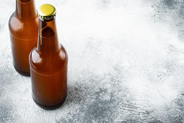 Bière fraîche dans des bouteilles en verre, sur table en pierre grise