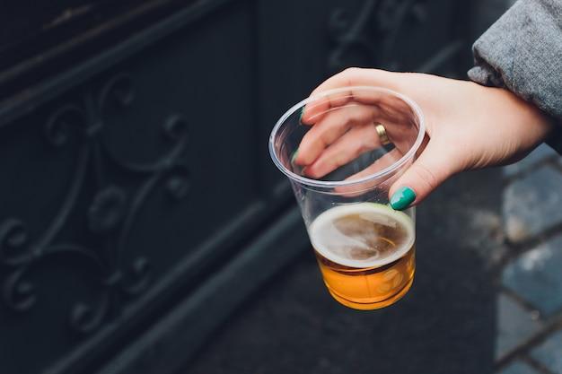 Bière fraîche dans une tasse en plastique dans une main.