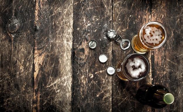 Bière fraîche dans un verre avec bouchons et ouvre-bouteille. sur un fond en bois.