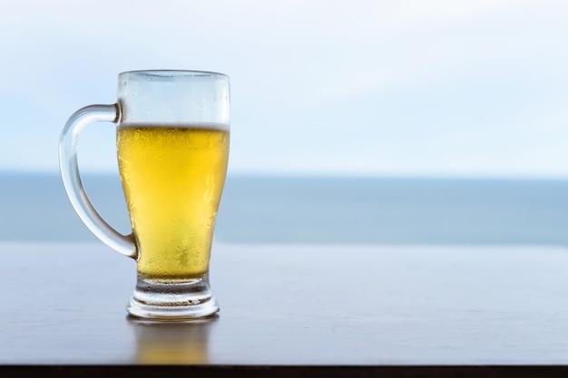 Bière fraîche fraîche en verre sur table avec horizon mer et ciel. vacances de vacances avec consommation d'alcool en été.