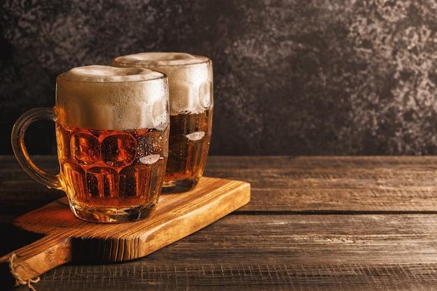 Bière froide en verre avec des frites sur une table sombre.