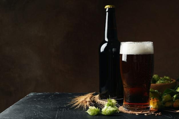 Bière, houblon et blé contre mur brun